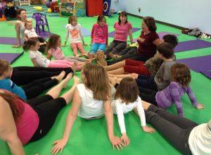 Kids in a yoga class practicing