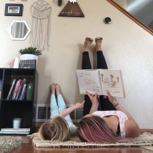 mom and young daughter reading book